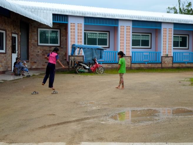 couple of young girls playing hop scotch on their school playground.
